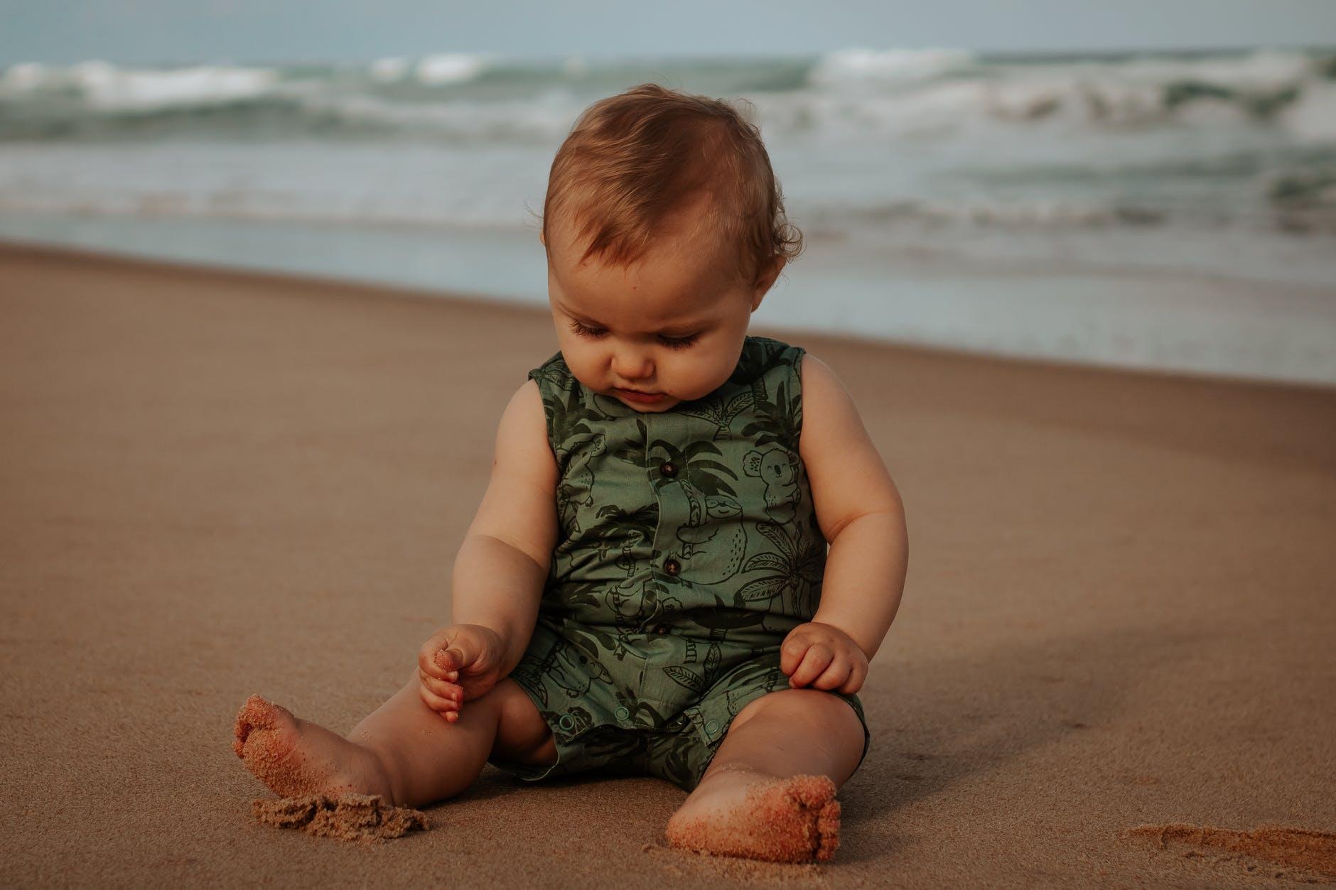 cute baby in ornamental wear resting on sandy sea shore