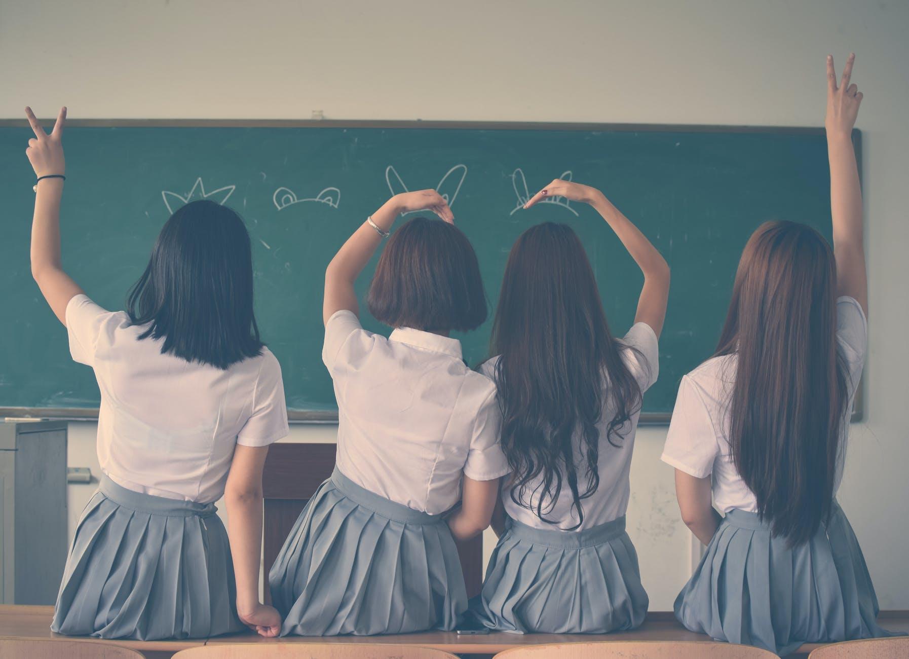 photo of four girls wearing school uniform doing hand signs