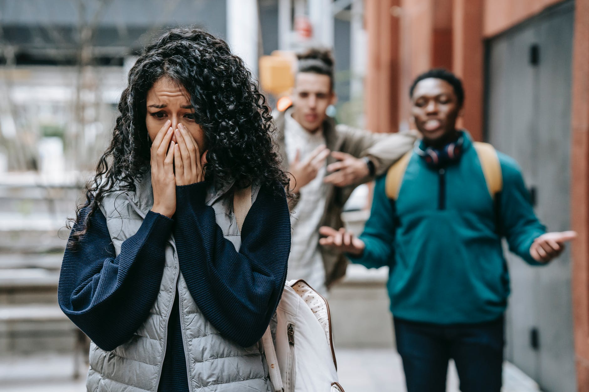 sad ethnic woman crying after being bullied by multiracial male students