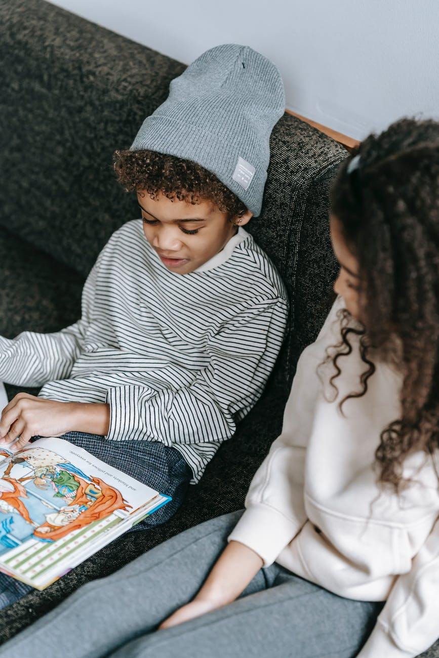 concentrated black children reading interesting book with different pictures