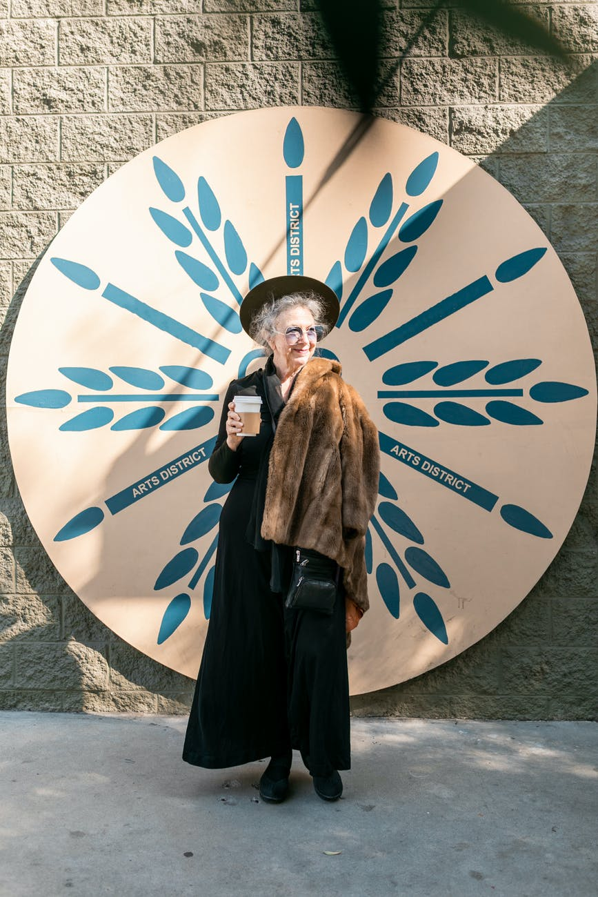 elderly woman in black standing beside white and blue round wall decor