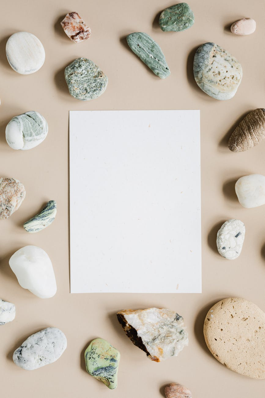 blank white sheet of paper on beige surface with stones