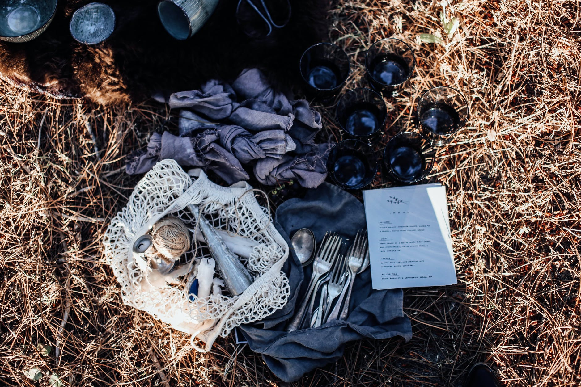 napkins and reusable bag near cutlery and glasses on grass