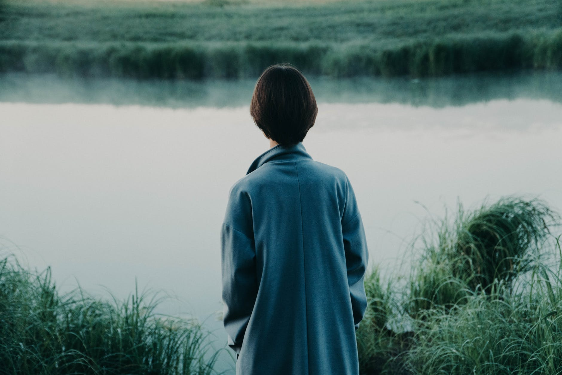 unrecognizable person contemplating pond and green grass