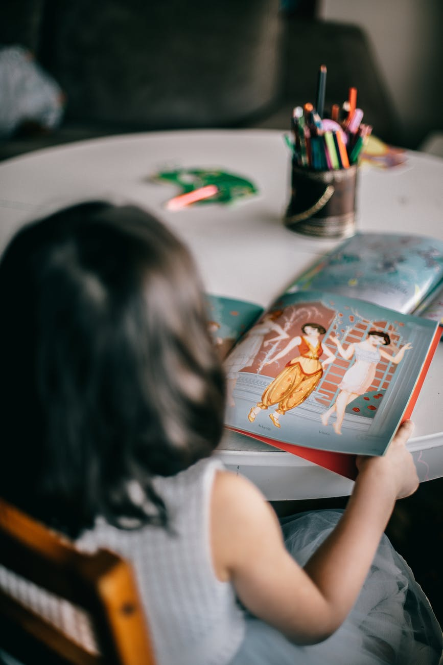 anonymous girl looking at picture in book