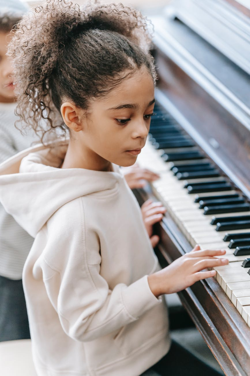 ethnic children playing piano in house