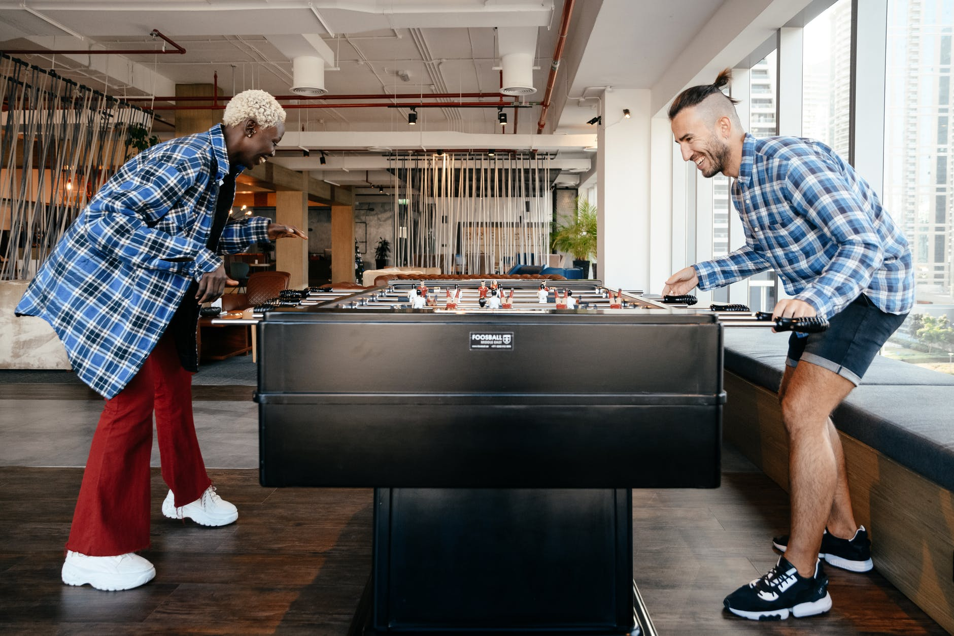 cheerful diverse friends playing foosball in living room
