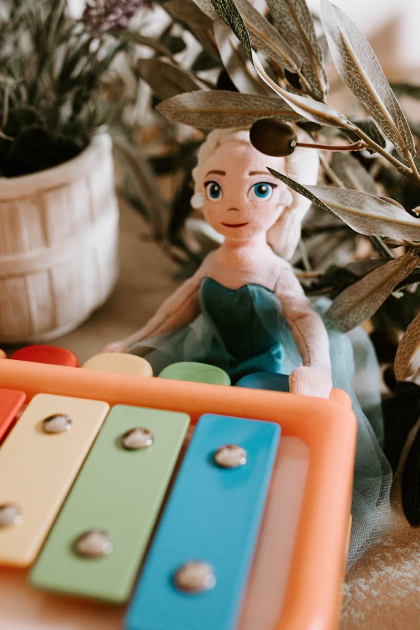 toy girl with musical instrument among plants