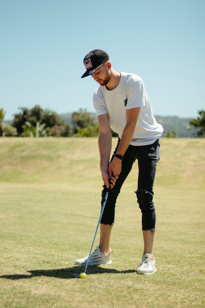 man playing golf in field in sunny day