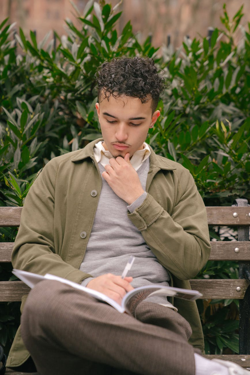 pensive ethnic male reading book on bench