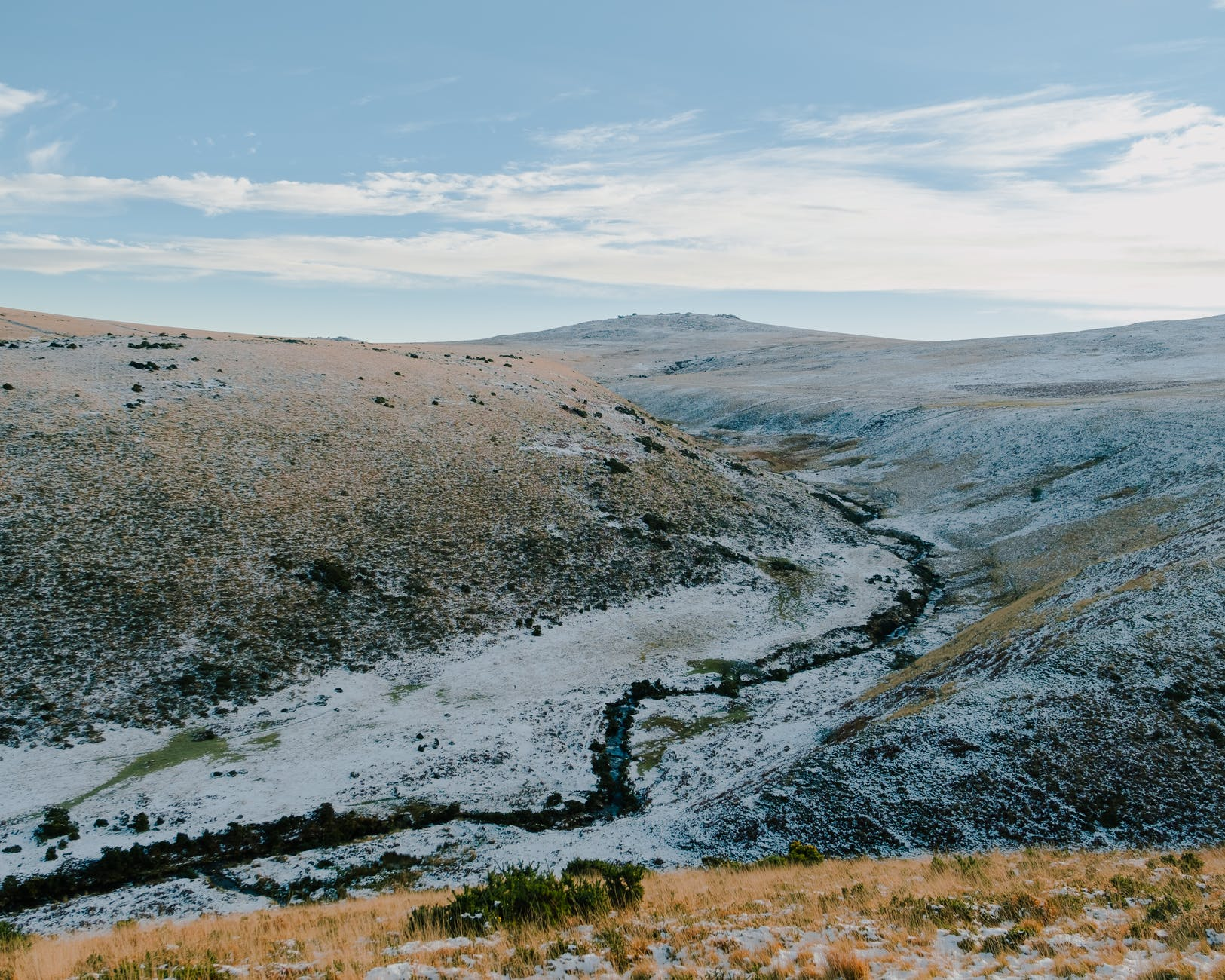 creek flowing through hilly terrain covered with snow