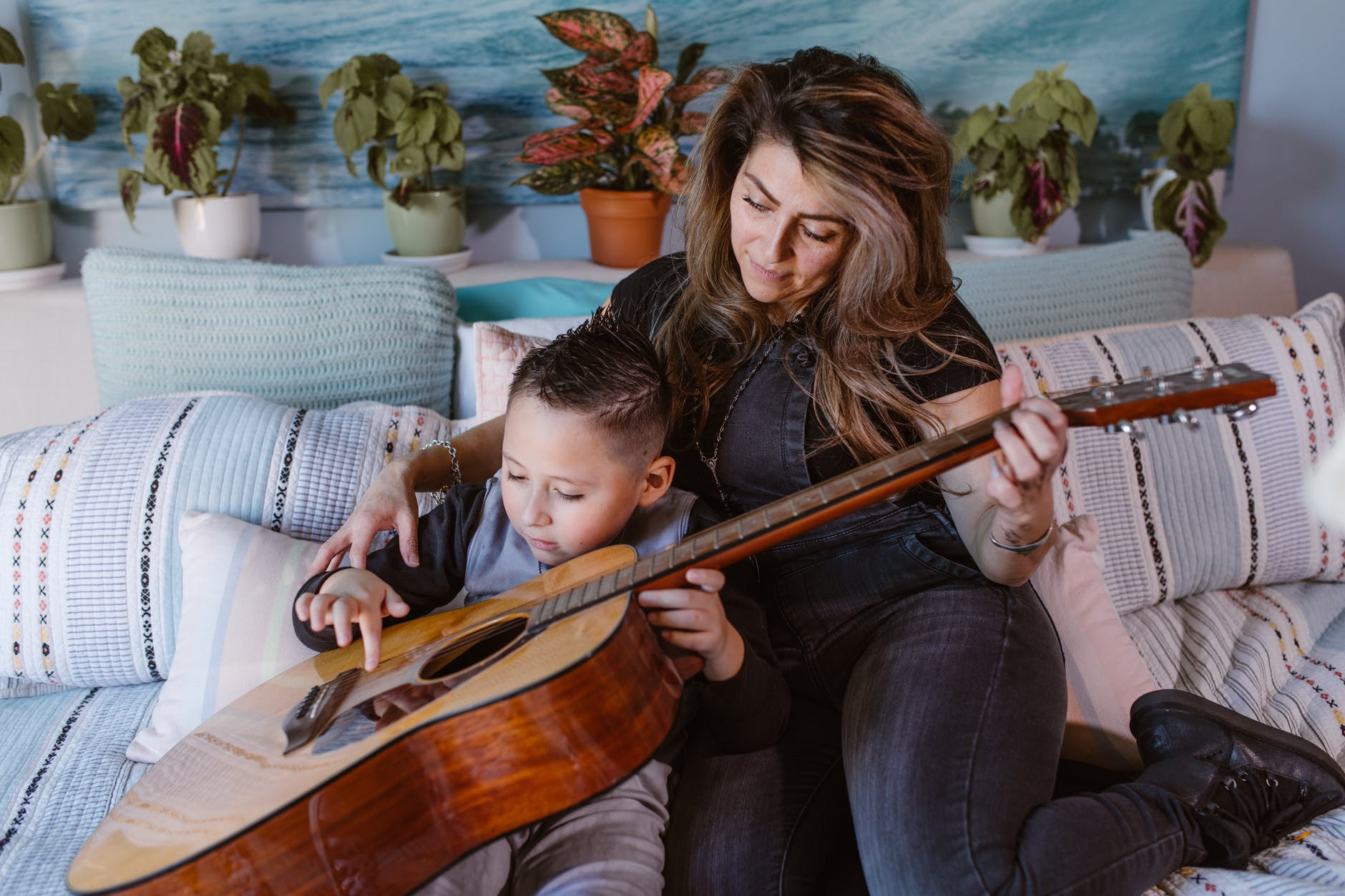 relaxed young woman playing guitar on bed with little son