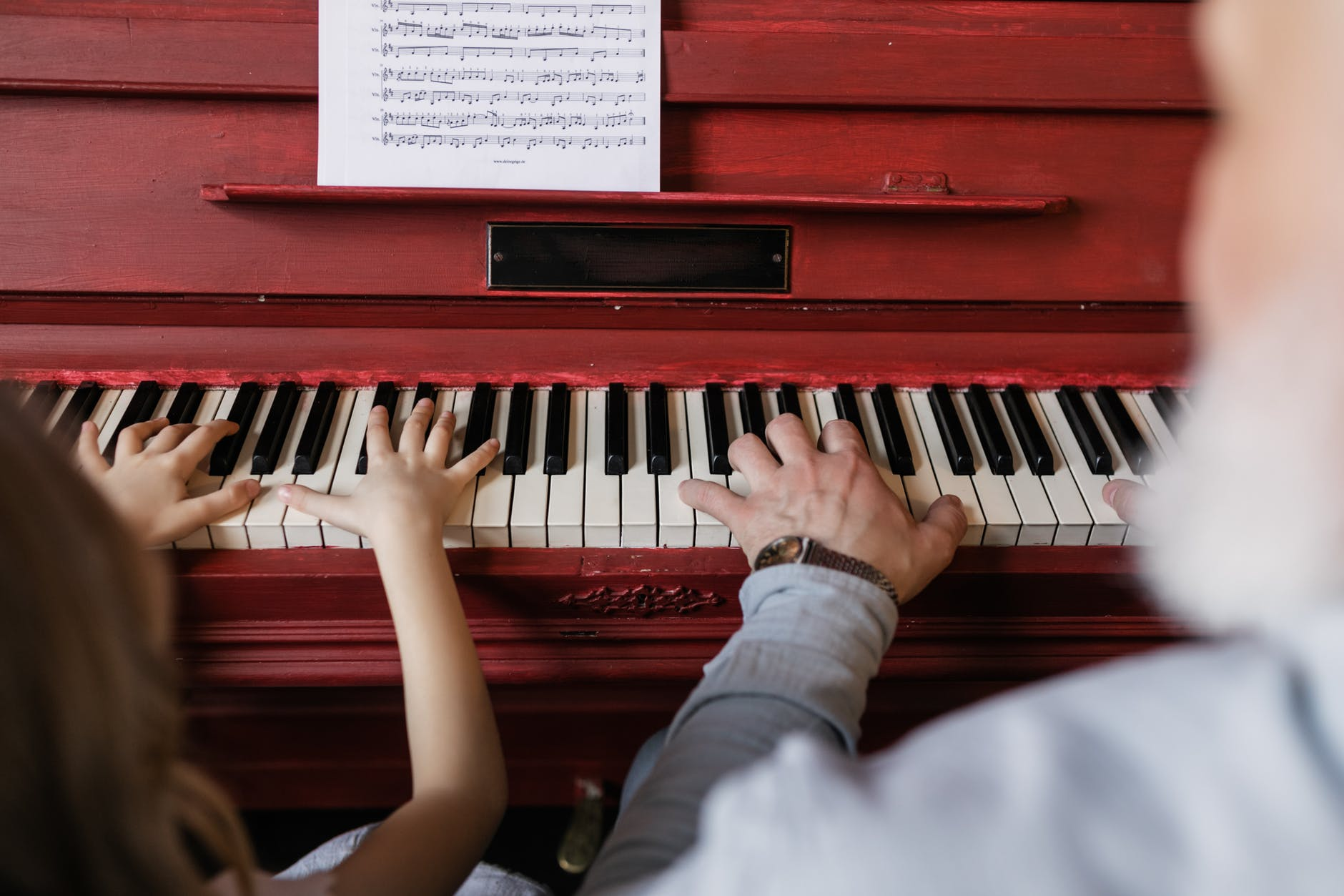 people playing piano with sheet music