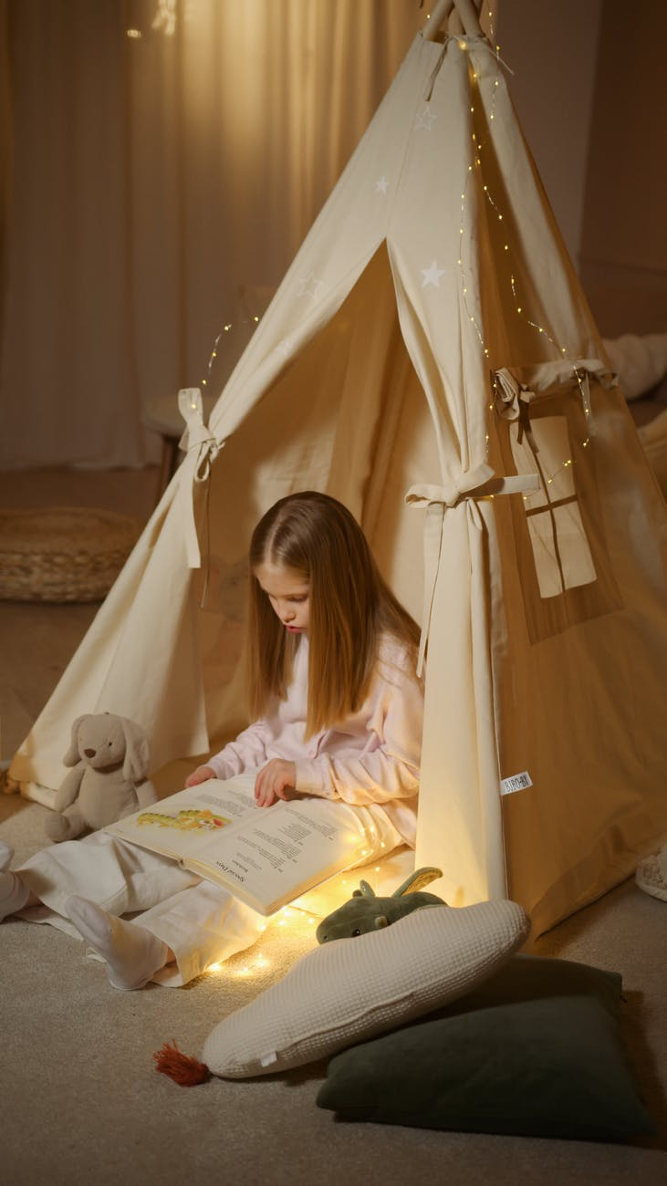girl in white long sleeve shirt sitting on yellow tent reading book