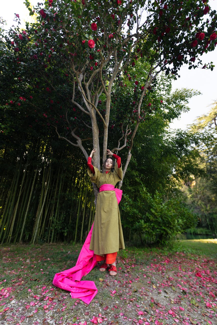 woman in green kimono standing under a flowering tree