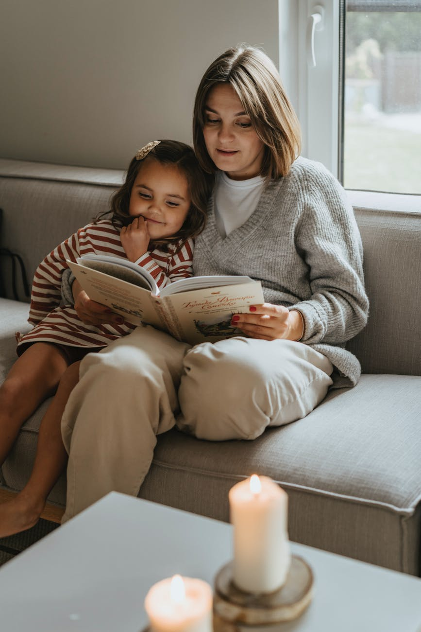 woman in gray sweater sitting on couch beside woman in gray sweater
