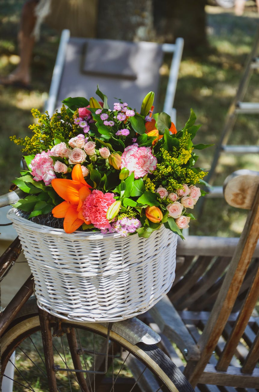 pink and yellow flowers in white woven basket